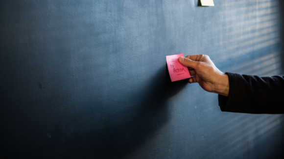Blackboard with hand placing pink sticky note